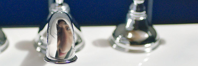 Reflexión del hombre en un grifo que brilla intensamente