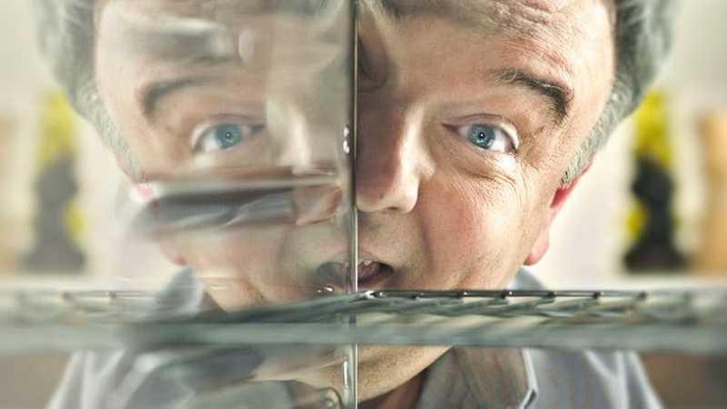 Hombre mirando en un horno con reflejo